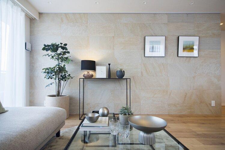 石壁をアクセントクロスに採用したリビング。上品な石目模様のタイルは、お気に入りのアートや小物を美しく引き立てて、高級感漂う空間になります。